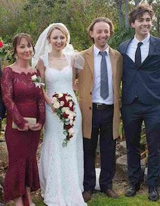 Mother of the Bride Customer wearing a wine red lace gown by Elle Zeitoune for her daughters wedding day