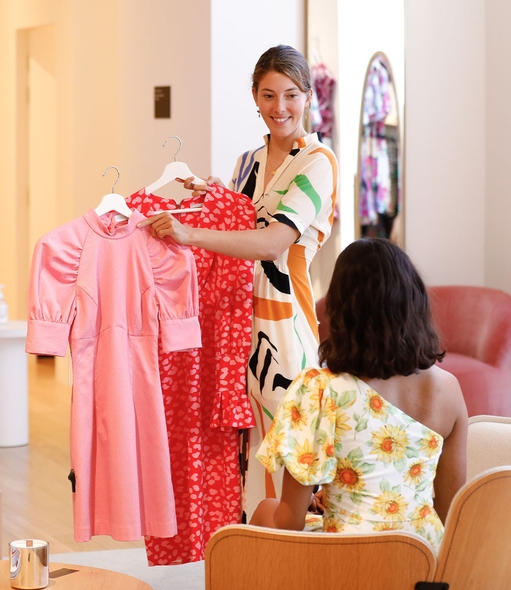 GlamCorner store employee presenting multiple dresses to a customer